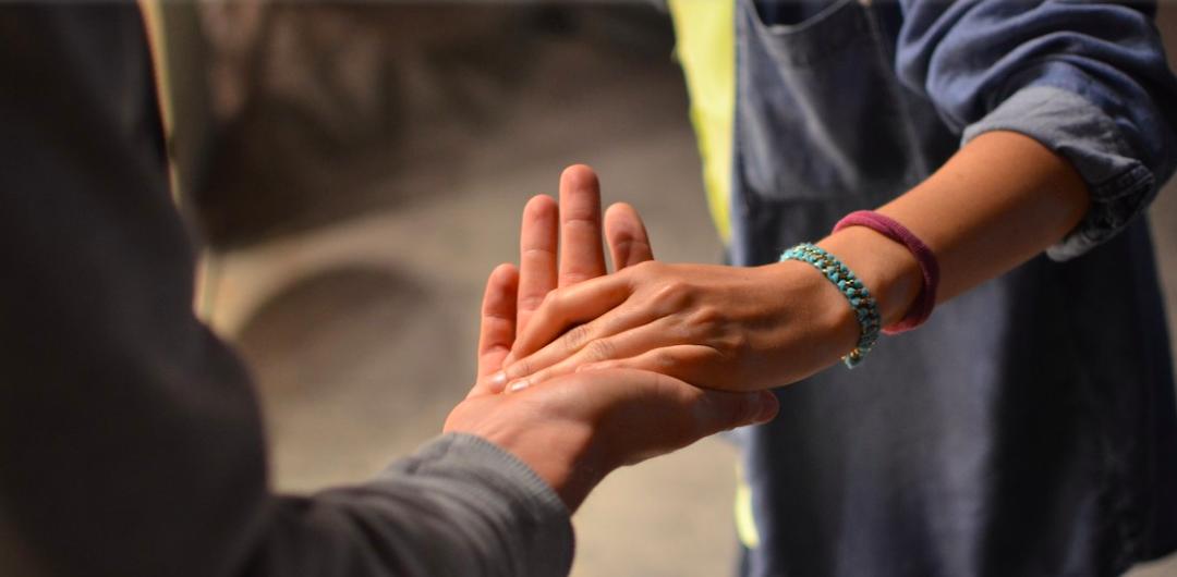 Una persona tende la mano ad un'altra persona in segno di aiuto.